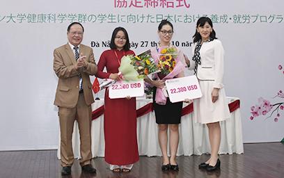 Bà Yuko Kamata - Giám đốc Điều hành Tập đoàn SEIREI (ngoài cùng bên phải) trao Học bổng cho Đoàn Nữ Nga My (áo dài đỏ) và Nguyễn Thị Lan Hương (thứ 2 từ phải sang)